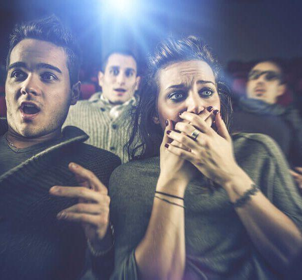 映画館で怖がるカップル