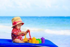 海でラッシュガードを着て遊ぶ赤ちゃん「