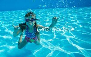 水着を着た子供の女の子が、プールで遊ぶシーン