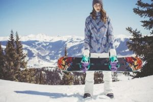 ゲレンデでスノーボードを持って立つ女性