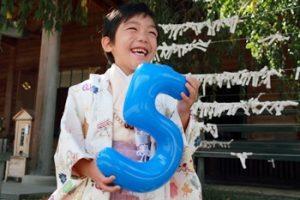 5歳男の子が七五三に着物を着て、「5」のバルーンを持っている