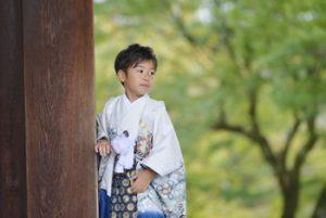 5歳男の子が七五三に着物を着て、神社の境内で撮影