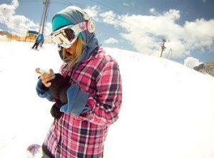 ゲレンデでスノボをする女性