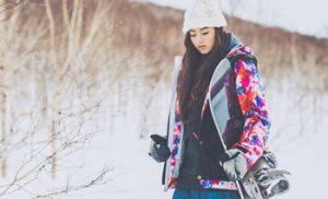 スノーボードを持って歩く女性