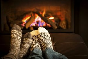 クリスマスに暖炉の前で温まるカップル