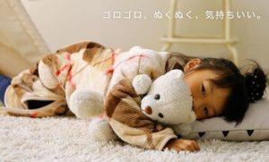 着る毛布を着て、寝転ぶ子供