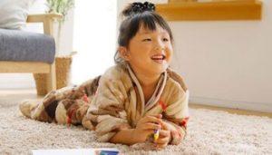 着る毛布を着て寝転ぶ女の子の子供
