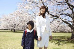 桜の下にスーツを着た母親とランドセルを背負う子供