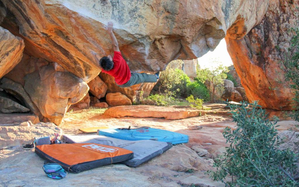 外岩でボルダリングをする男性
